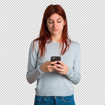 Jovem ruiva enviando uma mensagem ou e-mail com o celular