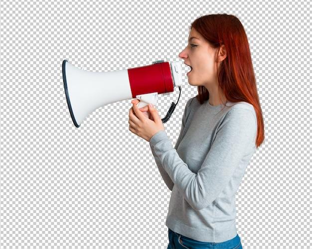 Jovem ruiva gritando através de um megafone para anunciar algo em posição lateral