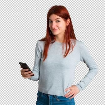 Jovem ruiva olhando para a câmera e sorrindo enquanto estiver usando o celular