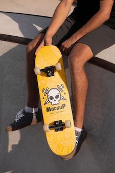Jovem segurando um skate mock-up