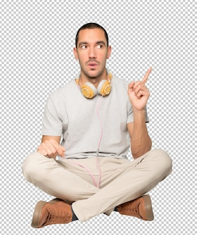Jovem sentado com um gesto de apontar o dedo