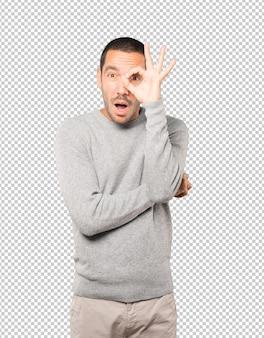 Jovem surpreso usando as mãos como um binóculo
