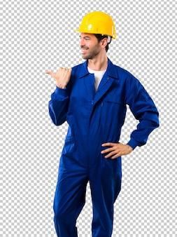 Jovem trabalhador com capacete apontando para o lado com um dedo para apresentar um produto