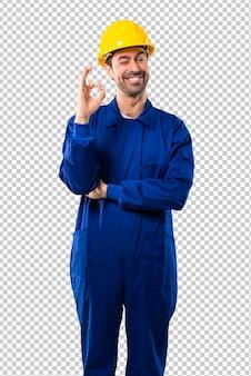 Jovem, trabalhador, com, capacete, mostrando, um, tá bom sinal, com, dedos, enquanto, piscando um olho