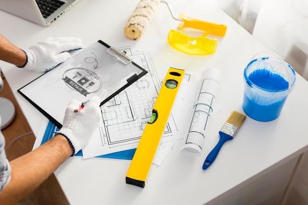Jovem trabalhador manual e ferramentas de pintura