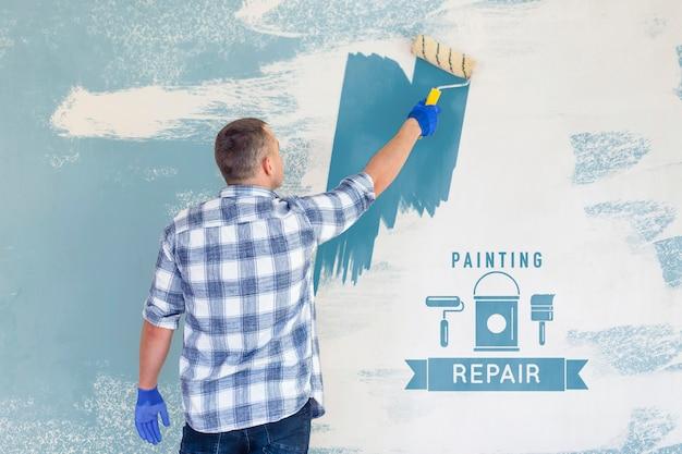 Jovem trabalhador manual pintando a parede de azul