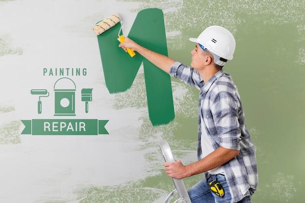 Jovem trabalhador manual pintando a parede em verde