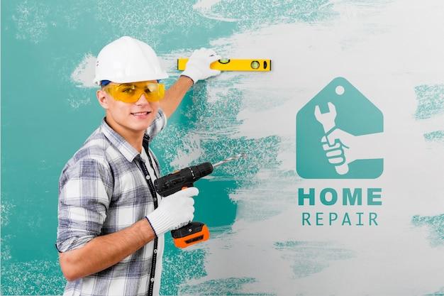 Jovem trabalhador manual segurando uma broca