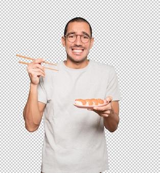 Jovem usando pauzinhos para comer sushi