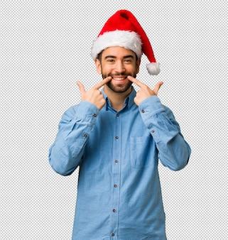 Jovem vestindo sorrisos de chapéu de papai noel, apontando a boca