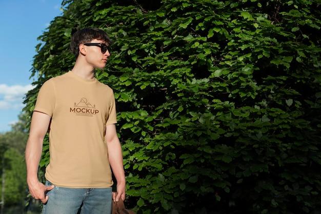 Jovem vestindo uma camiseta maquete do lado de fora