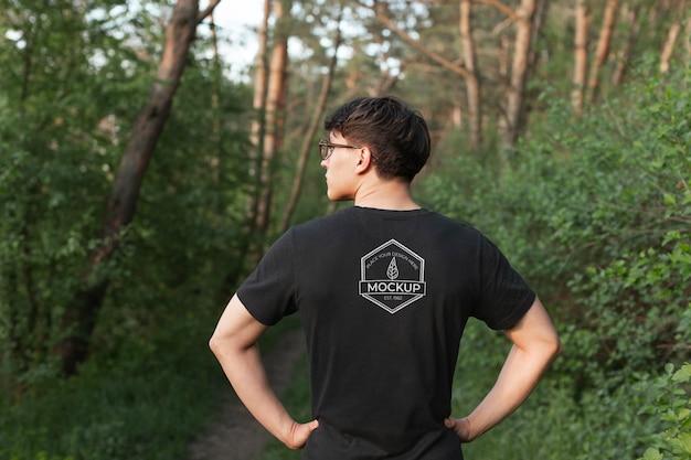 Jovem vestindo uma maquete de camiseta na floresta Psd Premium