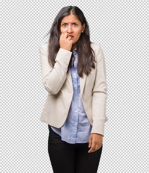 Jovens negócios mulher indiana roer unhas, nervoso e muito ansioso e com medo para o futu