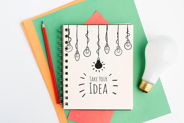 Lâmpada realista e bloco de notas com desenhos de lâmpadas
