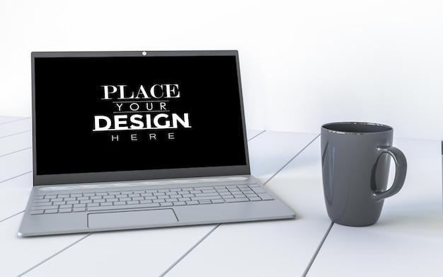 Laptop e caneca na mesa na maquete do espaço de trabalho
