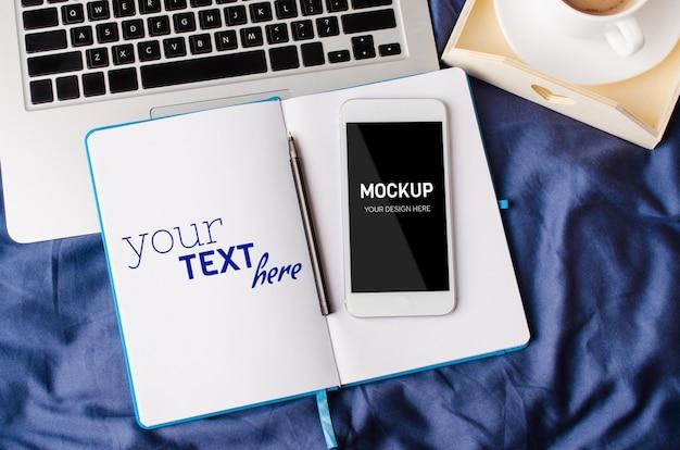 Laptop e smartphone, xícara de café e notebook na cama em tempo de manhã