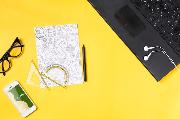 Laptop eletrônico na área de trabalho e folhas de papel