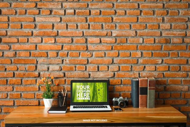 Laptop na mesa de madeira e maquete da parede de tijolo