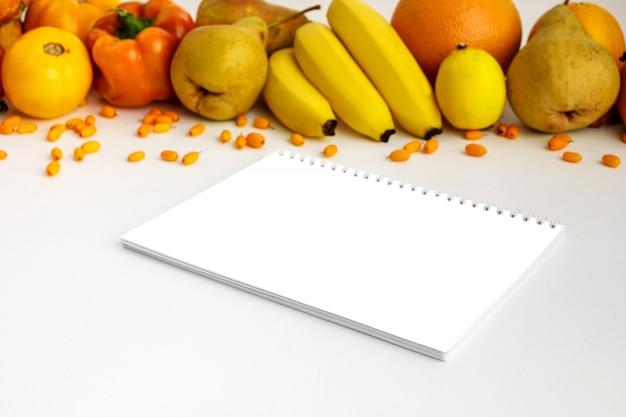 Legumes frescos amarelos e alaranjados do outono e frutas e caderno