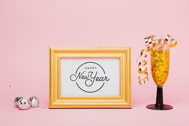 Letras de ano novo com confetes dourados em vidro