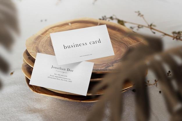 Limpe a maquete de cartão de visita mínima flutuando na placa de madeira