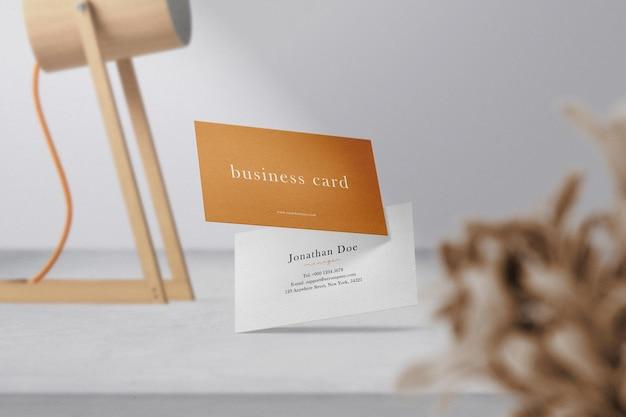 Limpe a maquete de cartão de visita mínima flutuando no cimento superior com lâmpada e folhas