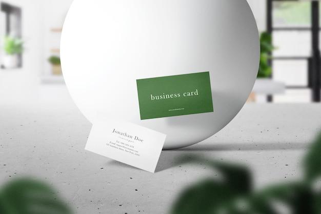 Limpe a maquete de cartão de visita mínima flutuando no cimento superior com uma esfera