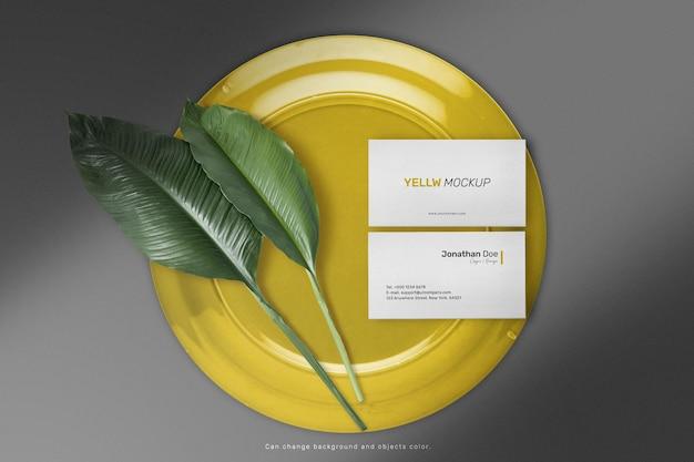 Limpe a maquete de cartão de visita mínima na placa de cor com folhas.