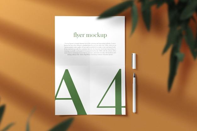 Limpe a maquete de folheto a4 mínima no fundo com caneta e folhas. arquivo psd.