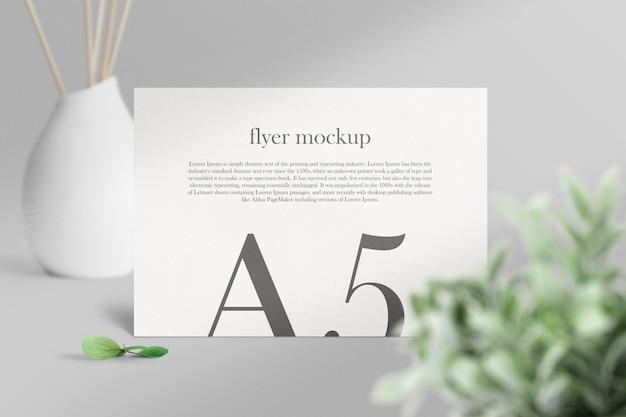 Limpe a maquete de panfleto a5 mínima no fundo com folhas e vaso. arquivo psd.