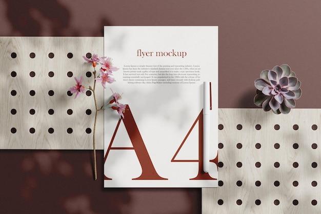 Limpe a maquete de papel a4 mínima na placa de madeira com plantas e flores