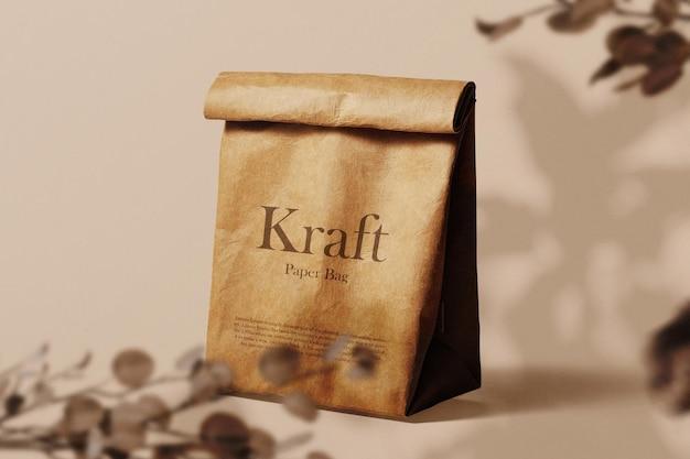 Limpe a maquete de saco de papel kraft mínimo no fundo com planta seca. arquivo psd.