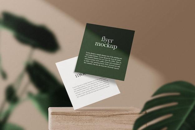 Limpe a maquete do panfleto quadrado mínimo flutuando no bloco de madeira com folhas.