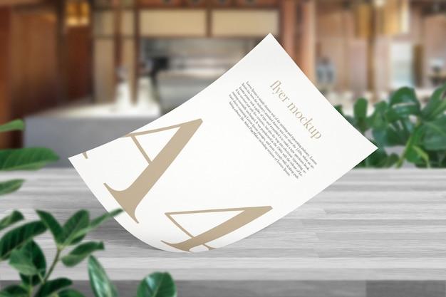 Limpe a maquete mínima de documento a4 na mesa de madeira no café branco.