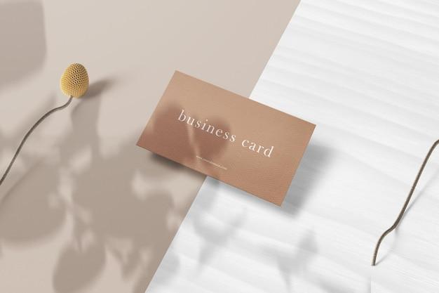 Limpe a maquete mínima do cartão de visita em madeira branca com flores