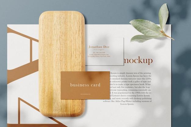 Limpe a maquete mínima do cartão de visita em uma placa de madeira com folhas