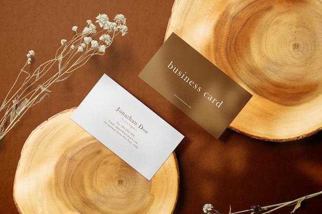 Limpe a maquete mínima do cartão de visita em uma placa de madeira com plantas secas
