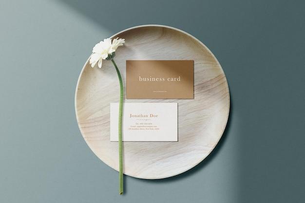 Limpe a maquete mínima do cartão de visita em uma placa de madeira com uma flor