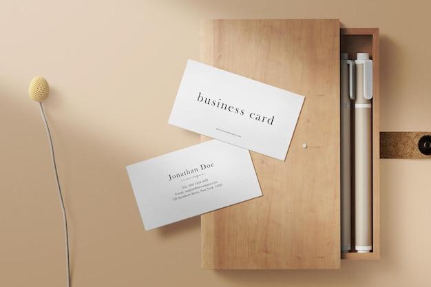 Limpe a maquete mínima do cartão de visita na caixa de lápis e na flor da planta