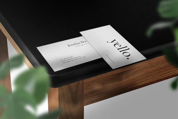 Limpe a maquete mínima do cartão de visita na mesa superior preta com folhas verdes
