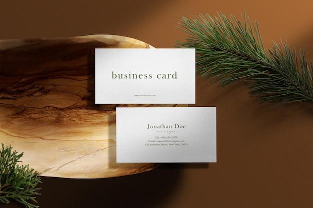 Limpe a maquete mínima do cartão de visita na placa de madeira com coníferas