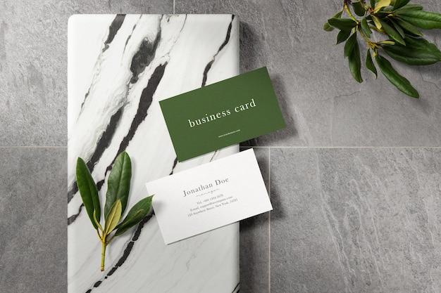 Limpe a maquete mínima do cartão de visita na placa de mármore com folhas
