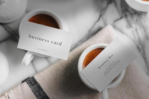 Limpe a maquete mínima do cartão de visita nas xícaras de café superiores