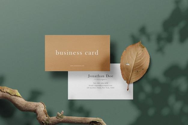 Limpe a maquete mínima do cartão de visita no fundo com galhos e folhas secas