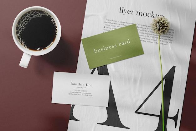 Limpe a maquete mínima do cartão de visita no papel com uma xícara de café e uma flor