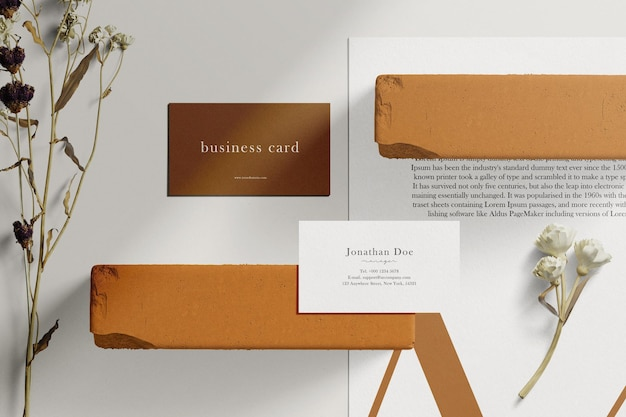 Limpe o cartão de visita mínimo e a maquete a4 de papel em um bloco de tijolos com folhas secas