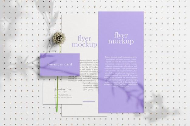 Limpe o cartão de visita mínimo e a maquete do panfleto no fundo com a flor
