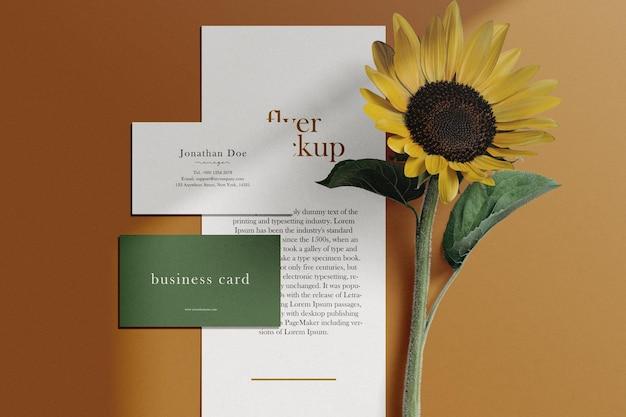Limpe o cartão de visita mínimo e a maquete do panfleto no fundo com girassol