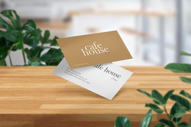 Limpe o modelo mínimo de cartão de visita na mesa de madeira no café branco.