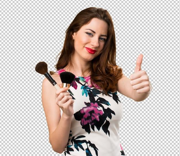 Linda garota com pincel de maquiagem com o polegar para cima